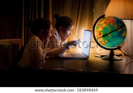 Two little sisters using laptop at night - stock photo