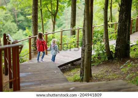 Two little sisters walking down stairs in summer park on beautiful sunny day - stock photo