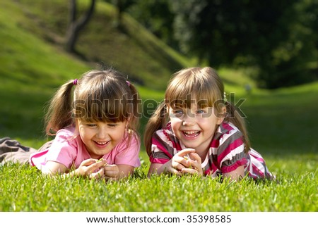 Two little smiling girls lying on the grass in the park