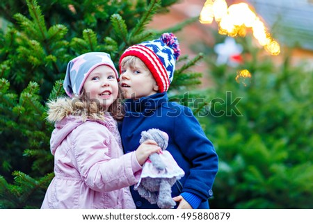 Two little smiling kids, boy and girl hugging on German Christmas market. Happy children in winter clothes with lights on background and xmas trees. Family funny brother and sister