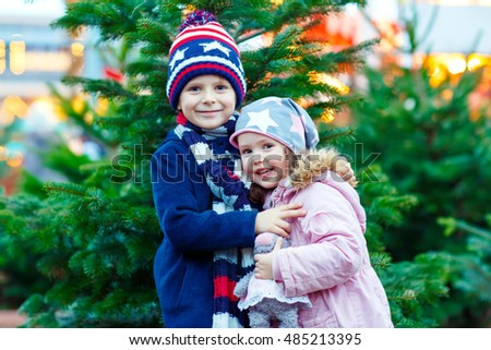 Two little smiling kids, boy and girl with christmas tree. Happy children in winter clothes on Christmas market with lights on background. Brother and sister looking at the camera.