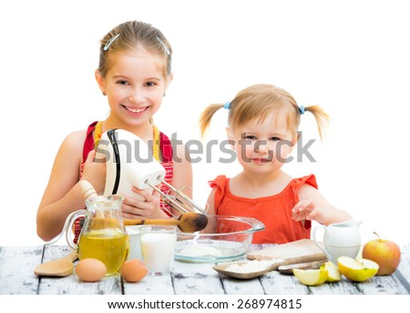 two little smiling sisters cooking isolated on a white background - stock photo