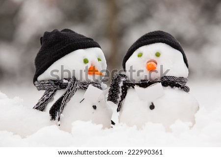 Two little snowmen in a group carol singing in the snow - stock photo