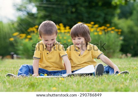 Two little sweet boys, brothers, reading a book in the park, summertime, late afternoon