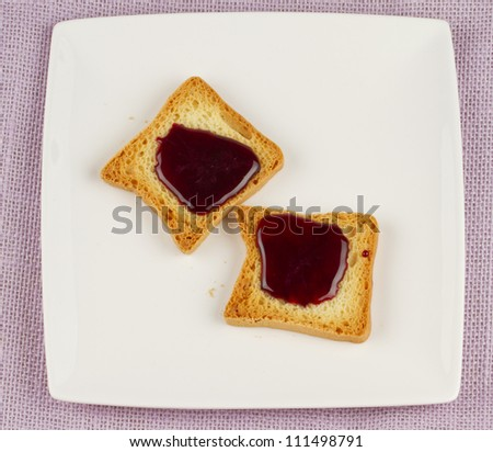 Two little toasts with rapsberry jam over white plate