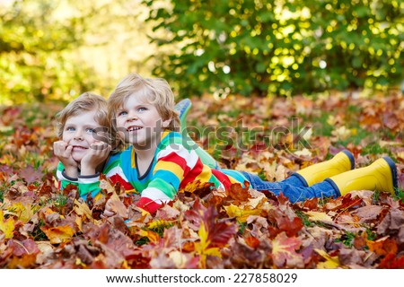 Two little twin boys lying in autumn leaves in colorful clothing. Happy siblings having fun in autumn park on warm day. - stock photo