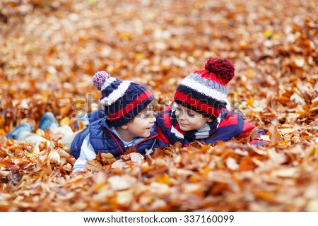 Two little twin boys lying in autumn leaves in colorful clothing. Happy siblings kids having fun in autumn forest or park on warm fall day. With hats and scarfs - stock photo