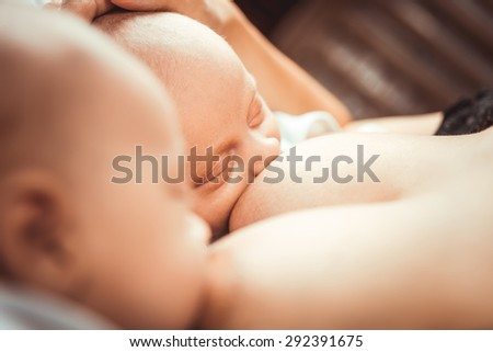 Two little twin suck the mother's breast - stock photo