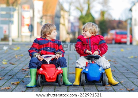 Two little twins and friends boys in red jackets and rain boots playing with colorful toy cars, outdoors. Kids leisure on cold day in winter, autumn or spring. - stock photo