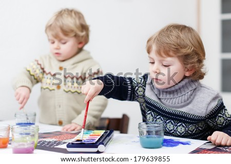 Two little twins boys having fun indoor, painting with different paints colors - stock photo