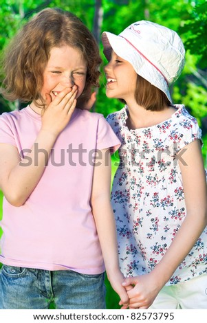 Two little whispering girls outdoors. - stock photo