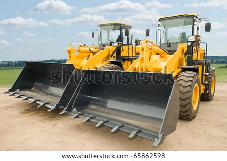 Two Loaders excavators construction machinery equipment outdoors - stock photo
