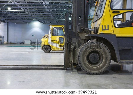 Two loaders in modern storehouse - stock photo
