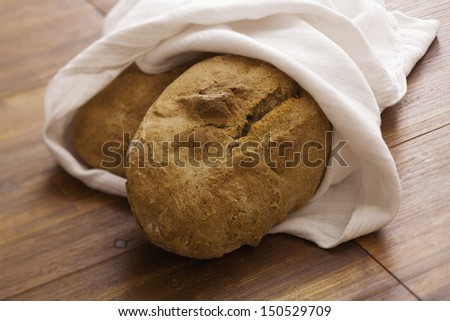 Two loaves of bread on cloth - stock photo