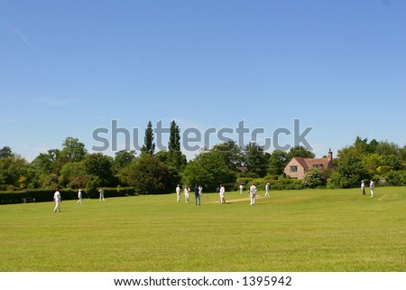 Two local cricket teams on a village green - stock photo