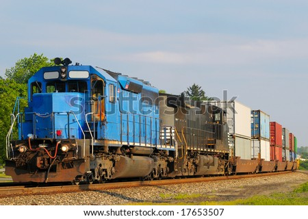 Two locomotives pulling a train of container cars - stock photo