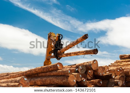 Two logs are lifted by a loader onto a pile of timber - stock photo