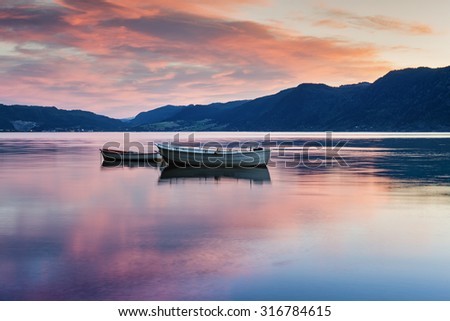 Two lonely boats on calm water of fjord. Norway. - stock photo