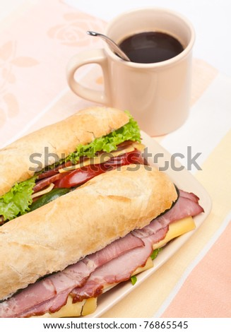 two  long baguette sandwich with lettuce, vegetables, salami and cheese and a cup of coffee - stock photo