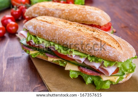 Two Long Ciabatta Sandwiches with lettuce, slices of fresh tomatoes, cucumber, ham, salami and cheese