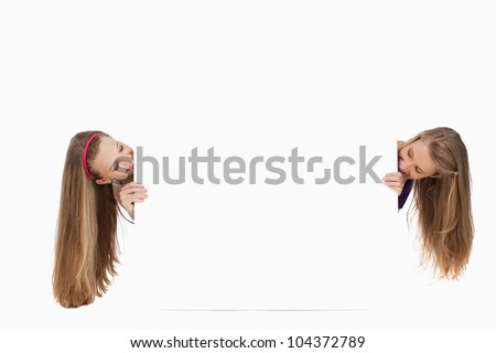 Two long hair young women behind a blank sign against white background - stock photo