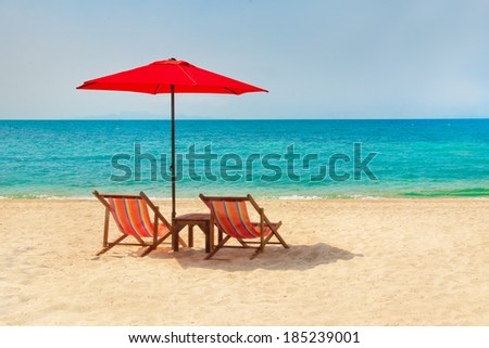 Two lounge chairs and a sunshade umbrella on the beach