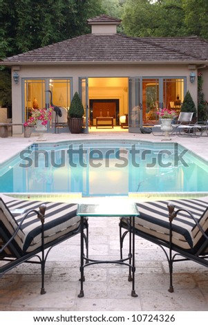 Two lounge chairs over look an inviting pool and a pool house - stock photo