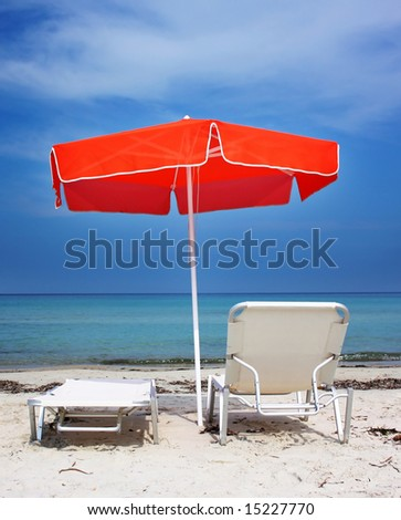 Two lounge chairs under a red umbrella on the sandy beach - stock photo