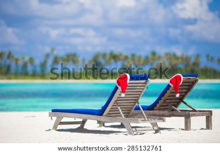 Two loungers with red Santa hats on tropical beach with white sand and turquoise water - stock photo