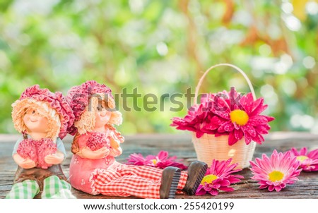 Two Lovely doll sitting and fresh flowers in a Basket on a wooden and bokeh background in a vintage retro style, with the sunrise, for the day of love, - stock photo