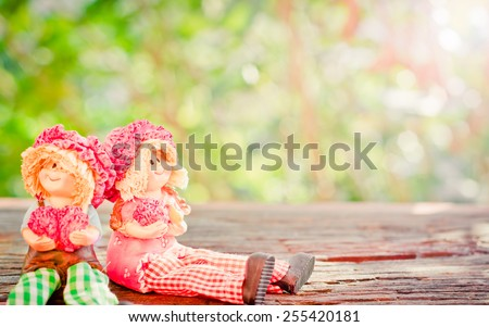 Two Lovely doll sitting on a wooden and bokeh background in a vintage retro style, with the sunrise, for the day of love, - stock photo