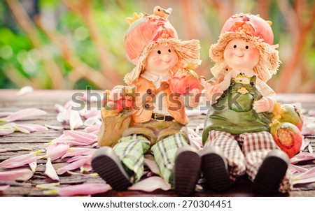 Two Lovely doll sitting on a wooden and  in a vintage retro style, with the sunrise,  - stock photo
