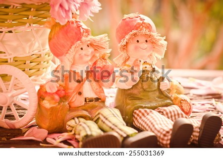 Two Lovely doll sitting on a wooden and tree background in a vintage retro style, with the sunrise, for the day of love - stock photo