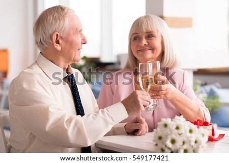 Two lovely elderly people holding up glasses of champagne