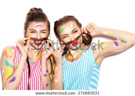 Two lovely girl friends having fun. Women smeared in paint show a mustache from the hair. White background not isolated - stock photo