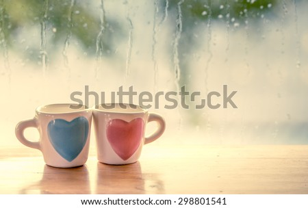 two lovely glass on rainy day window background  in vintage color tone - stock photo