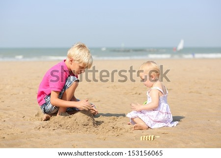Two lovely happy blond children, teenager boy and his little baby sister, playing together at the beach building sand castle, sea shore with yacht boats at the background - stock photo