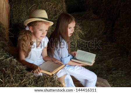Two lovely little girls with a beautiful smile reading a book in the hayloft in the village