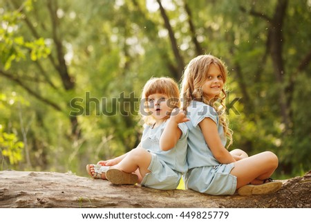 Two lovely little sisters sitting back to back on a fallen tree. Park on a sunny summer day. Family time. Soft focus