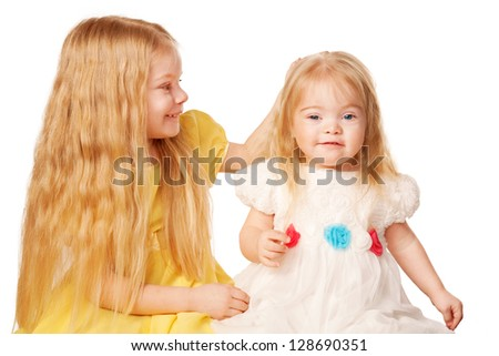 Two lovely sisters in elegant dresses. Preschooler and baby girl. Older sister stroking the head a little sister.  Isolated on white background
