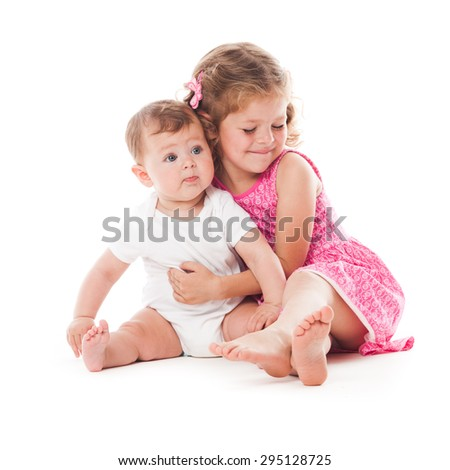 Two lovely sisters sitting on the floor and smiling isolated on white - stock photo