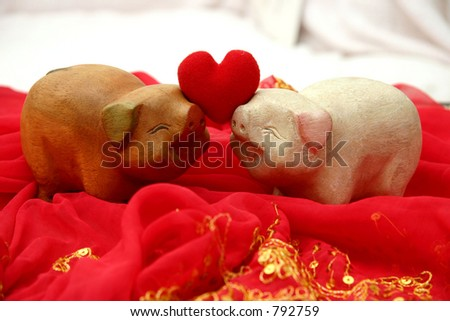 Two lovely smiling wooden pigs facing each other holding up a soft heart for Valentines - stock photo