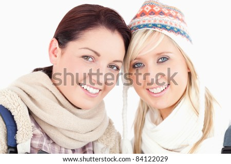 Two lovely women with heads together looking to camera