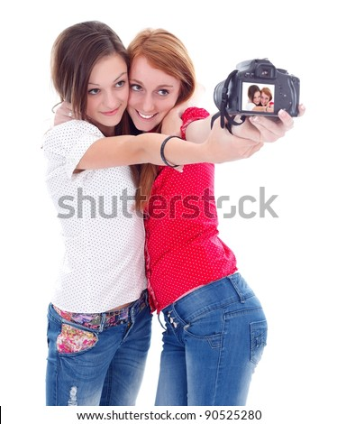 Two lovely young girls with camera taking photo about themselves - stock photo