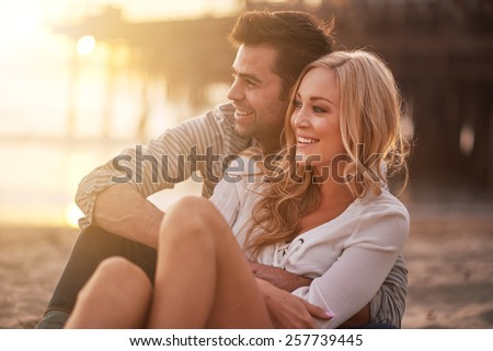 two lovers at santa monica beach holding each other with lens flare and warm image tone - stock photo