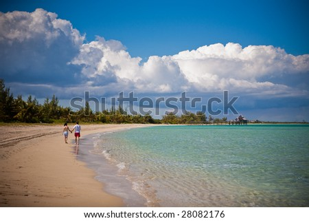 Two lovers going for a long walk down a Caribbean beach - stock photo
