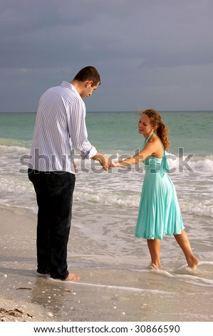two lovers holding hands and talking at the beach in the gulf of mexico in florida talking and holding hands, she appears to be trying to drag him into the water - stock photo