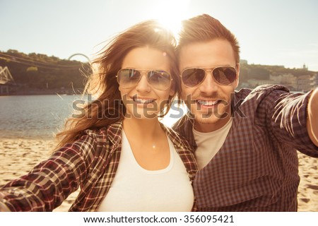 Two lovers making a selfie photo near the river, close-up photo - stock photo