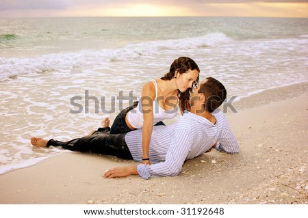 Two lovers on the beach, he is laying on his back, she is dripping wet between his legs making eye contact with him, they are wet from the ocean waves. In the background the sun is setting. - stock photo