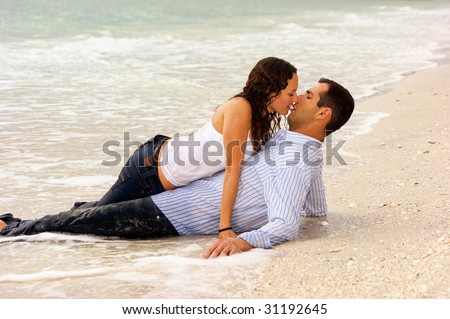 two lovers on the beach, laying in the water, the woman is dripping wet and laying on top of the man about to give him a kiss. - stock photo